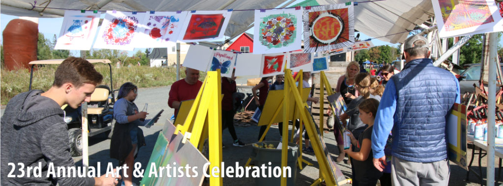 Visitors to the Franconia Art & Artists Celebration create their own art with spray paint and stencils. Yellow metal easels and finished artwork create color in the photograph.