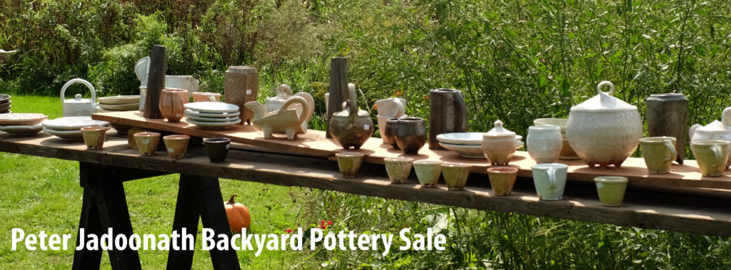 Functional pottery: vases, teapots, bowls, jars, plates and cups are set out on wooden planks supported by saw horses. The backdrop is wildflowers and trees.
